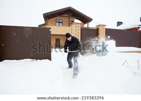 Man cleans snow shoveling around the house.  - stock photo
