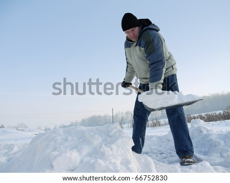 Man clearing path from snow with snow shovel after heavy blizzard - stock photo