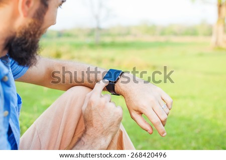 Man clicking on his smart watch. Template for smartwatch app design - stock photo