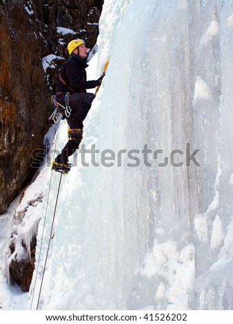 Man climbing a frozen waterfall
