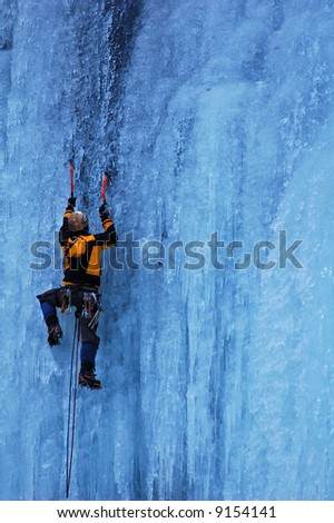 Man climbing a frozen waterfall - stock photo