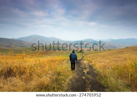 Man climbing a hill with colorful clouds - stock photo