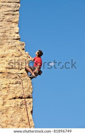 Man climbing a rock face next to the moon - stock photo