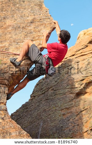 Man climbing a rock face with the moon in the sky - stock photo