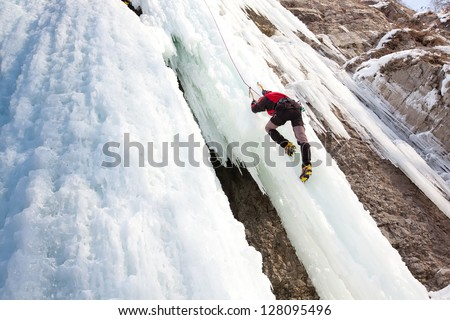 Man climbing frozen waterfall - stock photo