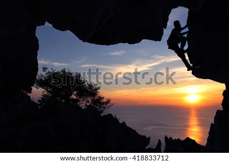 Man climbing in the cave on the mountain at sunset.