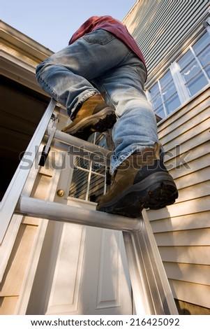 Man On Ladder Caulking Outside Window Stock Photo