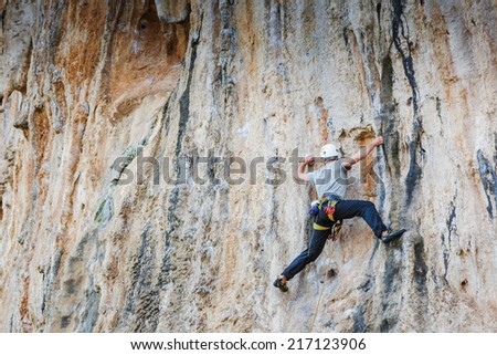 man climbing on rock. Adrenaline, strenght, ambition  - stock photo