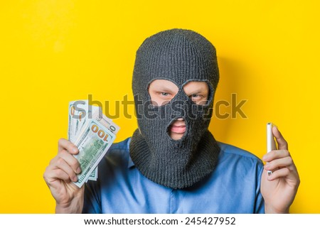 man close up thief in a mask and a blue shirt on a yellow background looking slyly at the camera, holding the money and the phone. Mimicry. Gesture. photo Shoot - stock photo