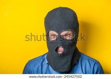 man close up thief in a mask and a blue shirt on a yellow background looks slyly to the camera. Mimicry. Gesture. photo Shoot/ evil criminal wearing balaclava - stock photo