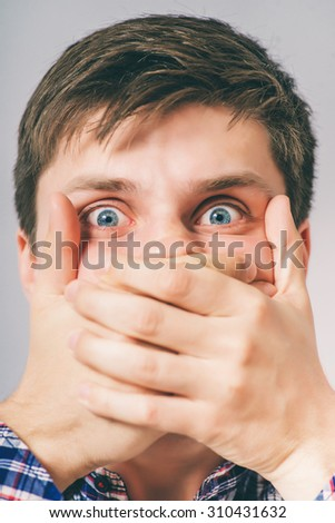 man closes the mouth with her hands - stock photo