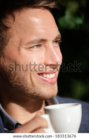 Man closeup portrait at cafe drinking coffee smiling happy. Handsome male model enjoying espresso at outdoor cafe in sun. - stock photo