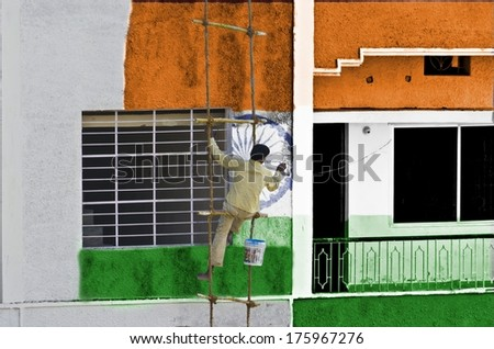Man coloring or painting Indian flag manually on wall hanging on a rope ladder - stock photo