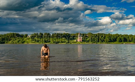 man comes out of the water against the background of the Orthodox Church, Russia, Volga river