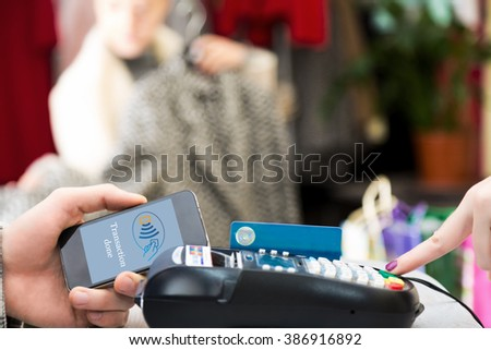 Man completing mobile Payment using modern smart Phone Technology at Store Cashiers Desk with Terminal Salesperson and female Customer interacting on Background - stock photo