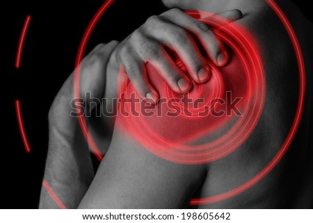Man compresses his shoulder, pain in the shoulder, black and white image, pain area of red color - stock photo