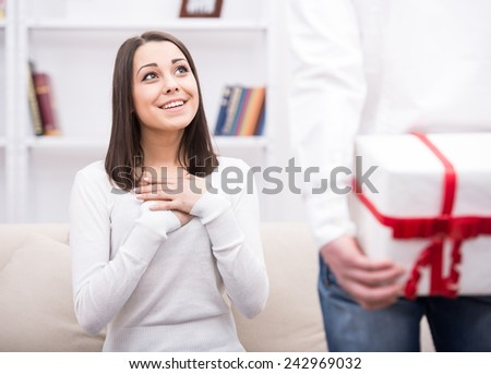 Man conceals the gift behind the back from his pretty girlfriend. - stock photo