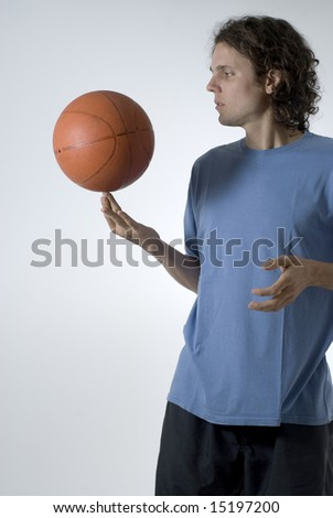 Man concentrates while balancing a basketball on his finger - Vertically framed photograph - stock photo