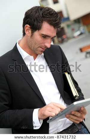 Man connected on internet with electronic tablet in town - stock photo