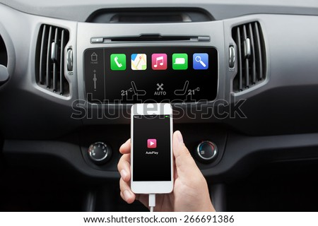 man connecting phone with auto play to the car media system - stock photo
