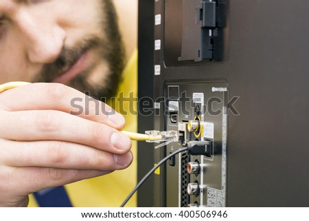 man connects internet cable to the TV - stock photo