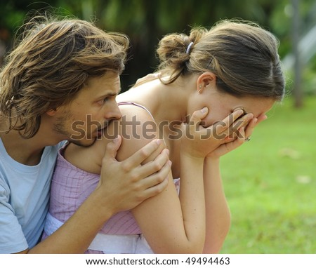 Man consoles his crying girlfriend in the park - stock photo