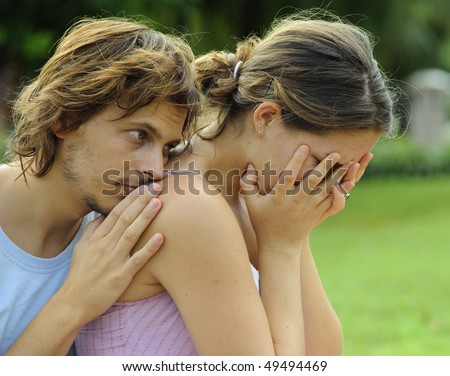 Man consoles his crying girlfriend in the park