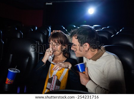 Man consoling woman crying while watching movie in cinema theater - stock photo