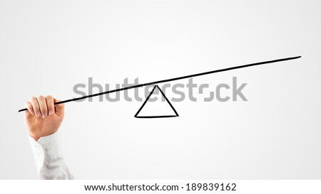 Man constructing a seesaw with a rod and triangle on a virtual interface to weigh up the balance between various concepts and see which carries the most importance on a white background with copyspace - stock photo