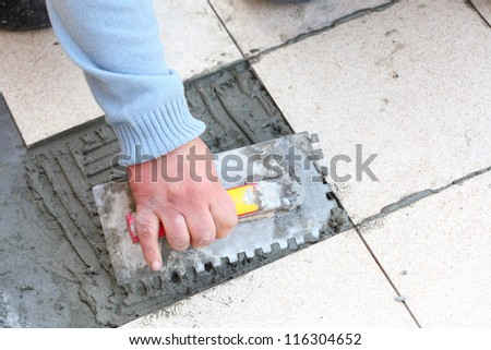 Man Construction worker is tiling at home