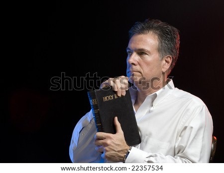 Man contemplating what he has just read in his bible, scene lit with red and blue gels. - stock photo