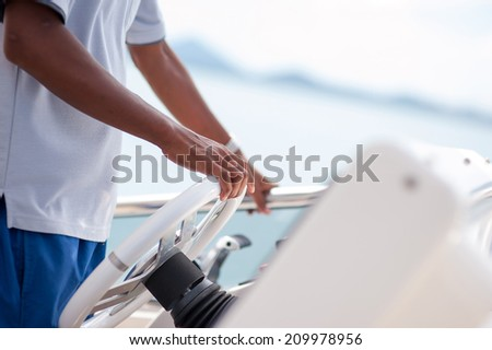 Man control the yacht wheel - stock photo