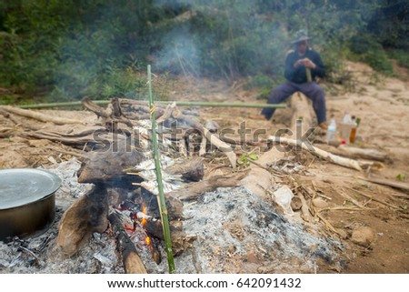 Man Cooking And Grilling Fish On Campfire In Forest