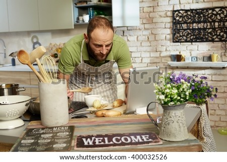 Man cooking at home in kitchen, using tablet computer.