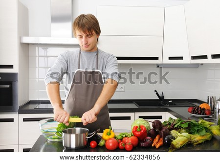 Man cooking in modern kitchen pasta and healthy vegetables - stock photo