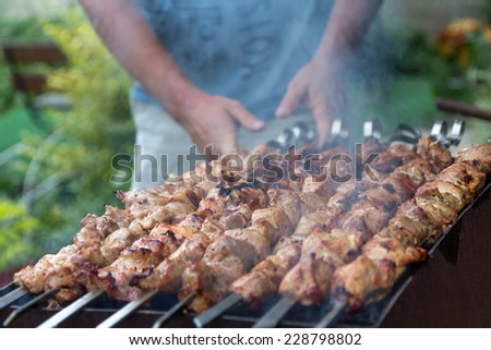 Man cooking kebab, meat grilling on metal skewer, close up