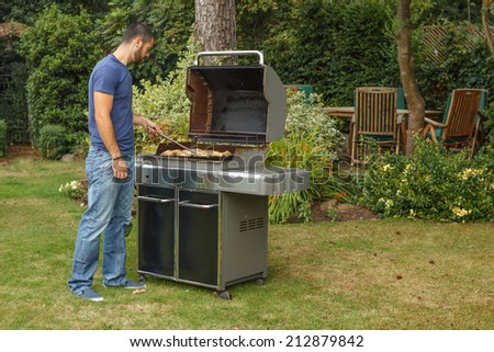 Man cooking meat on barbecue - stock photo