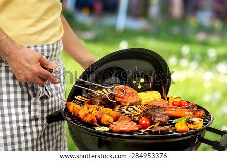 Man cooking meat on barbecue for family dinner - stock photo