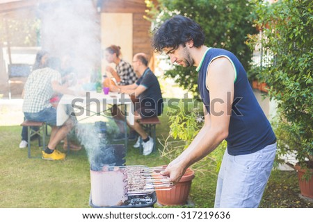 Man cooking meat on the barbecue. He, and the friends of him on background, are all on late twenties. They are eating outdoor on the grass. Everybody is wearing summer clothes. - stock photo