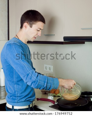 Man cooking scrambled eggs in pan at home kitchen