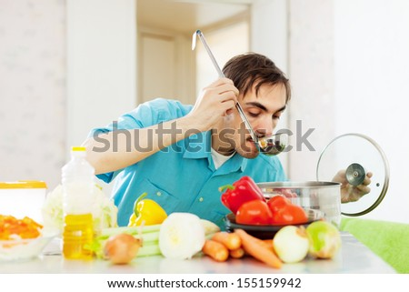 man cooks lunch with vegetables at kitchen - stock photo