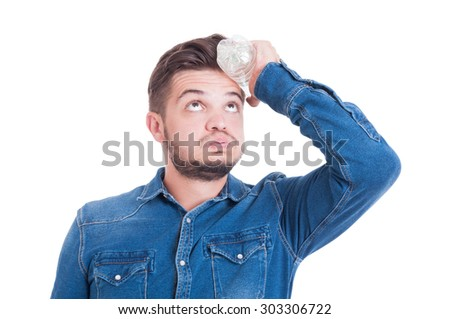 Man cooling his head with cold water bottle as summer heat concept - stock photo