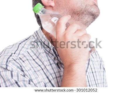 Man cooling his neck with a bottle of cold water as summer heat or heatwave concept - stock photo