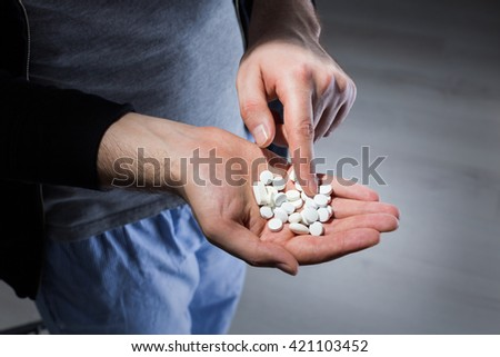 Man counting white pills on palm - stock photo