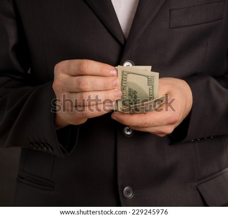 man counting your money, on a black background - stock photo