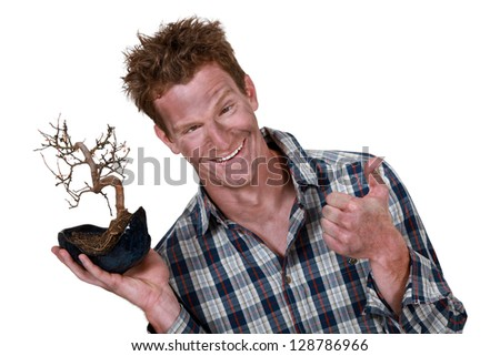 man covered with dust holding a plant root and making a thumbs up sign - stock photo