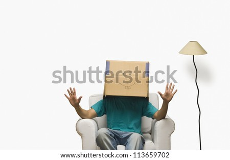 Man covering his face in a cardboard box - stock photo