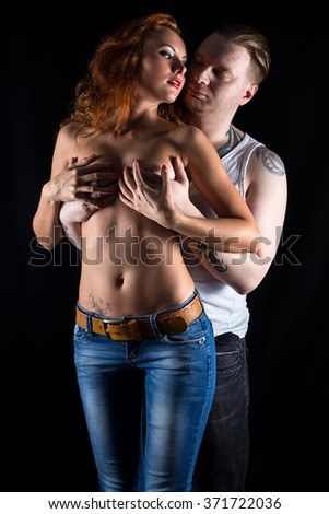 Man covering woman's chest on black background