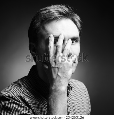 Man covers her eye with a hand - stock photo