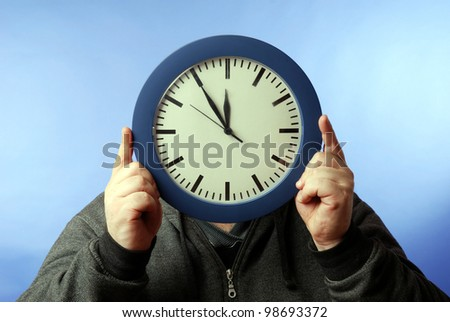 man covers his face with a clock - stock photo